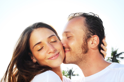 Close-up of a man kissing his girlfriend.